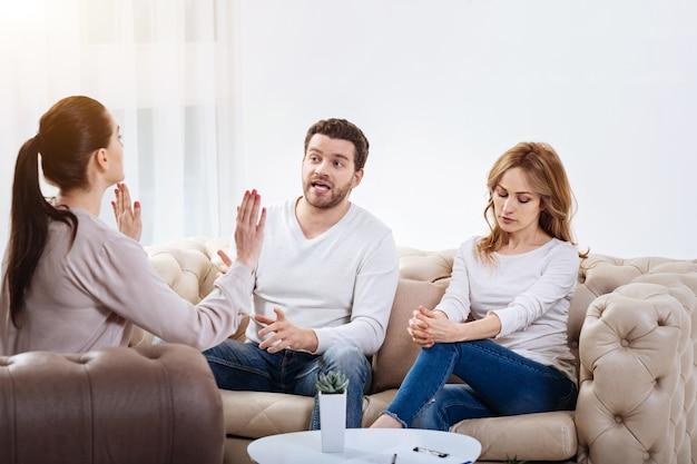 Smettere di combattere. fiducioso psicologo professionista femminile che tiene le sue mani davanti a lei e guarda i suoi pazienti mentre dice loro di smettere di combattere