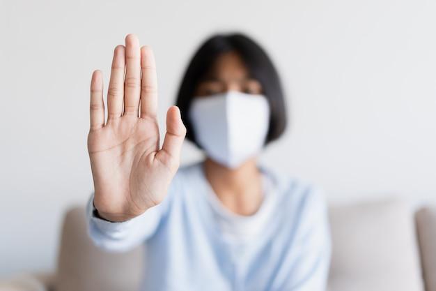 Ferma l'epidemia del virus della corona a mano. ragazza asiatica che indossa la maschera per proteggere lo scoppio e la quarantena a casa