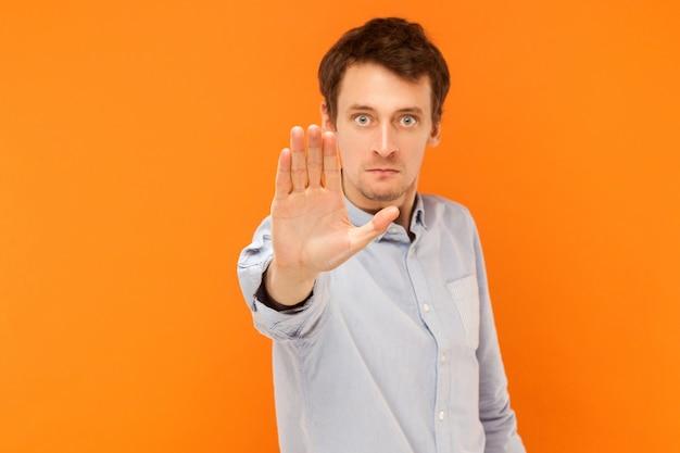 Ferma la mano. focus a portata di mano. linguaggio del corpo. foto in studio, sfondo arancione