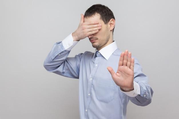 Fermati, non voglio vedere questo. bello uomo d'affari di setole in camicia blu in piedi, coprendosi gli occhi e bloccando con le mani il gesto di arresto. indoor studio shot, isolato su sfondo grigio copyspace.