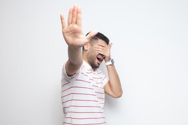 Fermati, non voglio guardare questo. ritratto di un giovane barbuto confuso con una maglietta a righe in piedi, che si copre gli occhi e mostra il gesto di arresto. girato in studio al coperto, isolato su sfondo bianco.