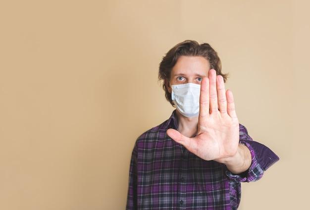Ferma l'infezione. uomo in buona salute che mostra gesto - stop. foto di uomo indossa una maschera protettiva contro malattie infettive e influenza. concetto di assistenza sanitaria. focalizzazione morbida