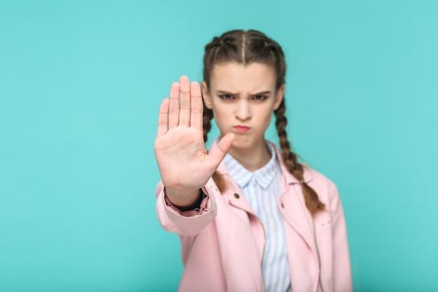 Smettila, ritratto serio di bella ragazza carina in piedi con trucco e acconciatura a codino marrone in giacca rosa camicia a righe azzurre. indoor, studio shot isolato su sfondo blu o verde.
