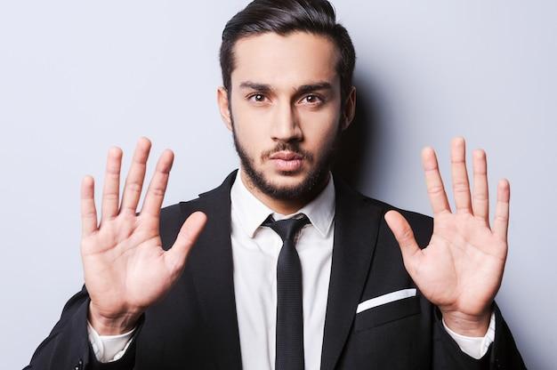 Smettila! giovane serio in abiti da cerimonia che mostra i palmi delle mani e guarda la telecamera mentre si trova in piedi su uno sfondo grigio