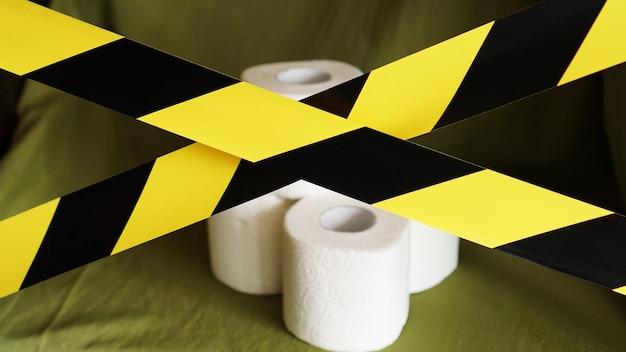 Stop al panico - coronavirus. rotoli di carta igienica dietro il nastro giallo