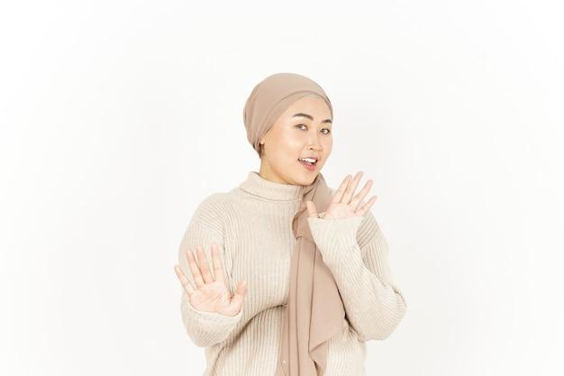 Arresto o gesto di rifiuto della bella donna asiatica che indossa l'hijab isolato su sfondo bianco
