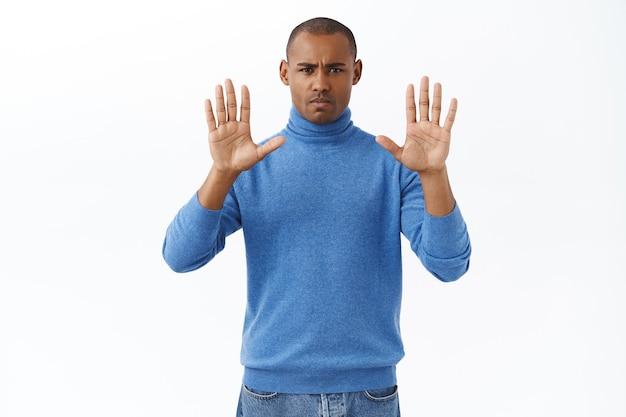 Fermati lì, basta. un uomo afroamericano fiducioso arrabbiato dall'aspetto serio che dice di smettere, proibire e avvertire