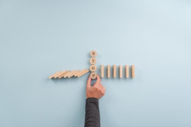 Segnale di stop nel mezzo di domino che crollano