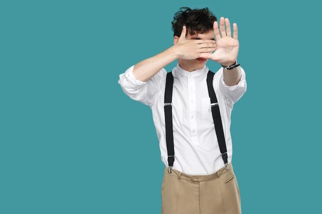 Segnale di stop. no, non voglio vedere questo. ritratto di giovane uomo d'affari riccio hipster bello in camicia bianca casual classica e reggicalze in piedi. colpo dello studio dell'interno isolato su priorità bassa blu.
