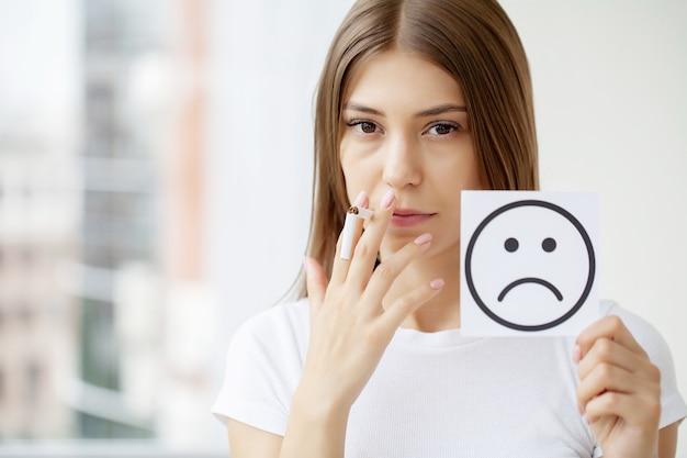 Smetti di fumare, donna che tiene una sigaretta rotta e una carta con un sorriso