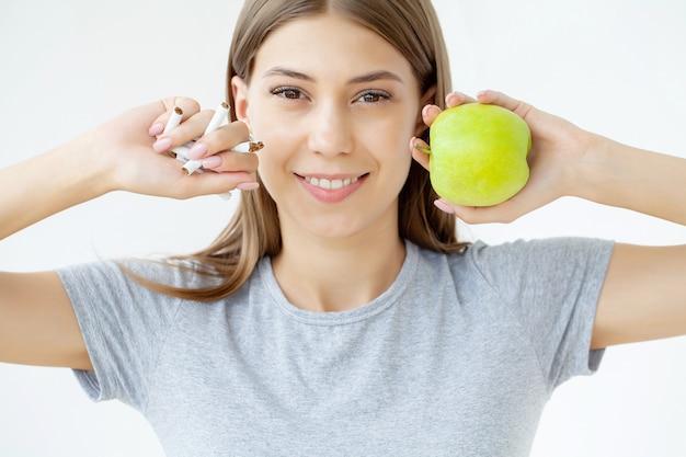 Smetti di fumare, donna che tiene una sigaretta rotta e una mela verde