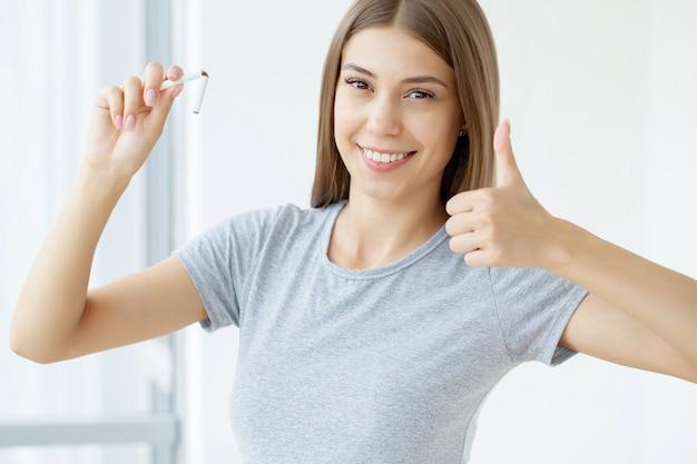 Smetti di fumare, donna che tiene in mano una sigaretta rotta