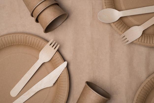 Smetti di usare il concetto di plastica. in alto sopra la foto vista dall'alto di posate in legno e bicchieri e piatti di carta isolati su un tavolo di sfondo di carta artigianale