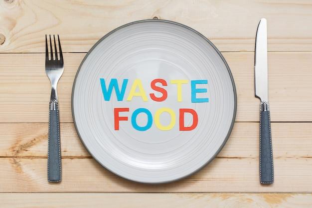 Smetti di sprecare cibo. l'iscrizione delle lettere ha tagliato di cartone colorato su un piatto e le coltelleria su un fondo di legno