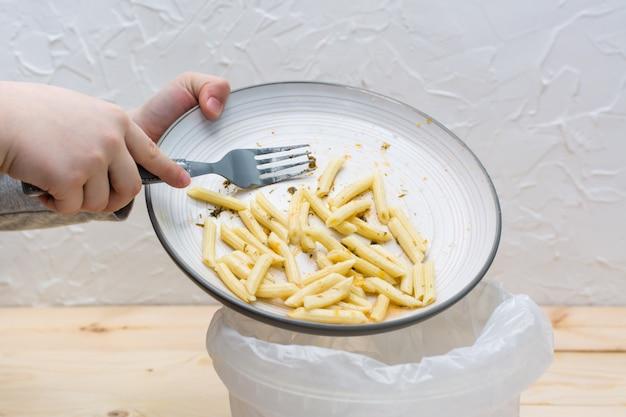 Smetti di sprecare cibo. il pranzo rimanente viene scaricato nel cestino.