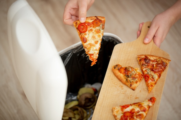 Smetti di sprecare cibo, mano della donna che getta del cibo, pezzi di pizza nel cestino, spazzatura, concetto di cibo