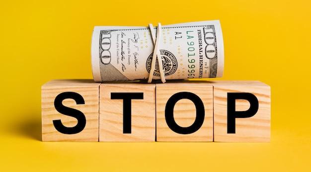 Stop con i soldi su uno sfondo giallo. il concetto di affari, finanza, credito, reddito, risparmio, investimenti, scambio, tasse