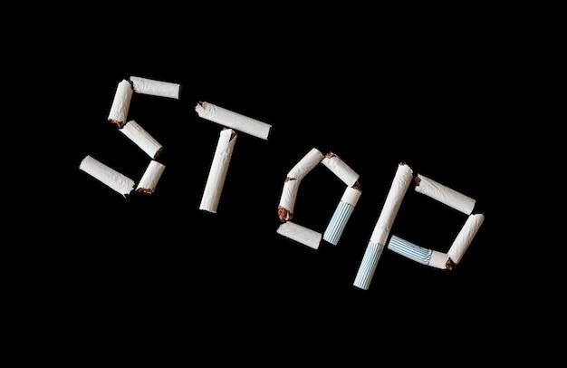 Ferma la parola dalle sigarette isolate su sfondo nero.