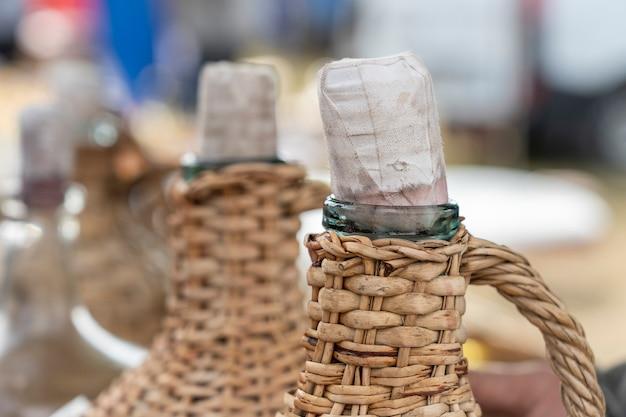 Il tappo e il collo di una bottiglia di vino in vimini sullo sfondo, primo piano