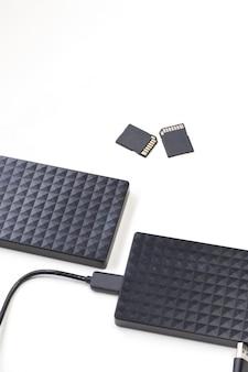 Dispositivo di archiviazione disco rigido esterno nero e schede sd isolate su computer a parete bianca