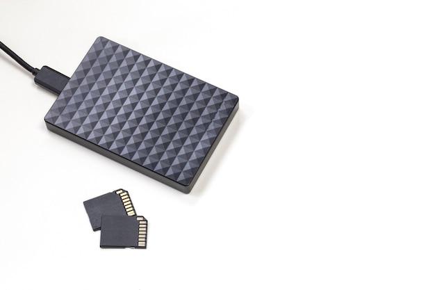 Dispositivo di archiviazione disco rigido esterno nero e schede sd isolate su muro bianco