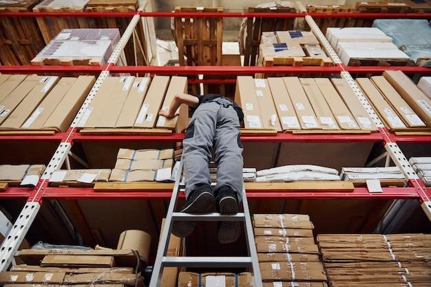 L'addetto allo stoccaggio si trova sulla scala in uniforme e blocco note in mano e controlla la produzione.