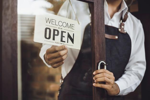 Proprietario del negozio che gira il cartello aperto largo attraverso il vetro della porta e pronto per il servizio.