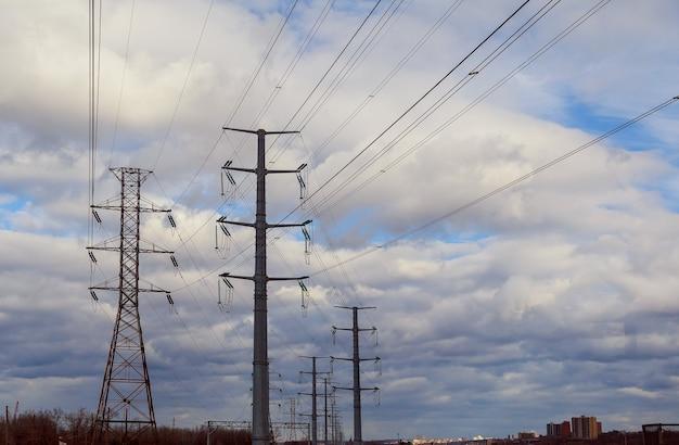 Cielo di nuvole temporalesche poli elettrici linee elettriche ad alta tensione sullo sfondo di un cielo tempestoso