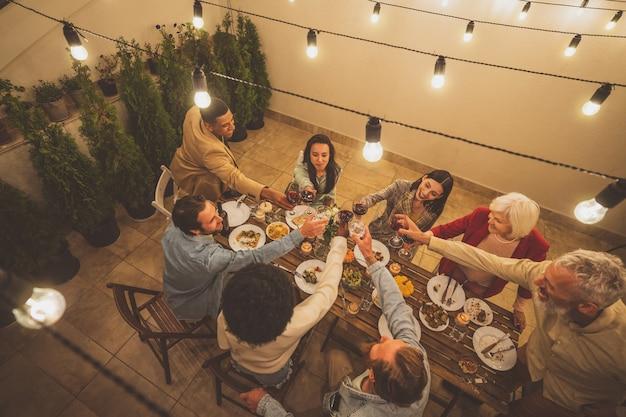 Riprese narrative di un gruppo multietnico di persone che cenano su un tetto. la famiglia e gli amici si riuniscono a casa