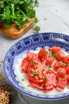 Insalata di stracciatella con pomodori e watermalone e ingredienti sul tavolo di cemento leggero