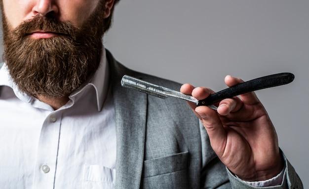 Rasoio a mano libera, barbiere, barba. rasoio a mano libera vintage. taglio di capelli da uomo. uomo nel negozio di barbiere.