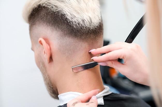 Rasoio a mano libera. processo di taglio di capelli del giovane biondo nel salone del barbiere, concetto di barbiere per uomini e ragazzi