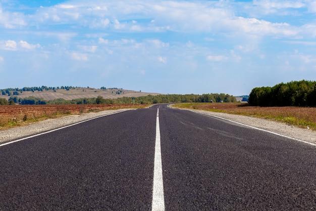 Strada diritta con una marcatura sullo sfondo della natura. strada aperta in futuro, niente auto, auto su strada asfaltata attraverso una foresta verde, alberi. nuvole sul cielo azzurro in estate, sole, giornata di sole. vista dal basso