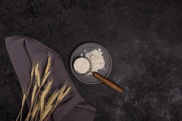 Un colino con manico in legno con farina in una piastra di cemento su sfondo nero. spighe di grano e un tovagliolo di lino. preparazione al forno