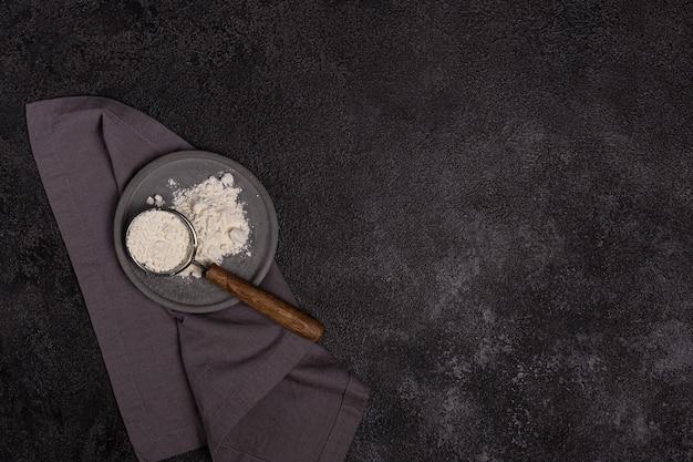 Un colino con manico in legno con farina in una piastra di cemento su sfondo nero