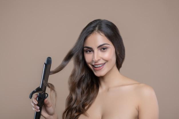 Ciocca di capelli. bella donna sorridente dai capelli lunghi con spalle nude e sguardo espressivo che tiene ciocca di capelli in ferro arricciacapelli