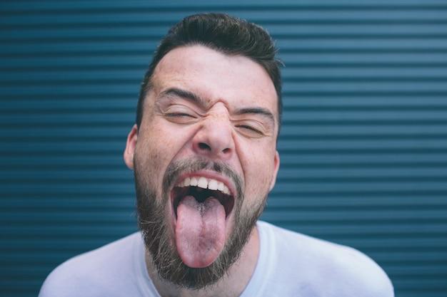 Strano uomo è in piedi dentro e mostra la lingua. sta guardando la telecamera e tiene gli occhi parzialmente chiusi. inoltre mostra i suoi denti. isolato su strisce