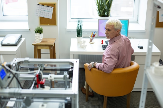 Strani suoni. uomo anziano dai capelli bianchi seduto al tavolo e guardando la stampante 3d, allertato dai suoi strani suoni