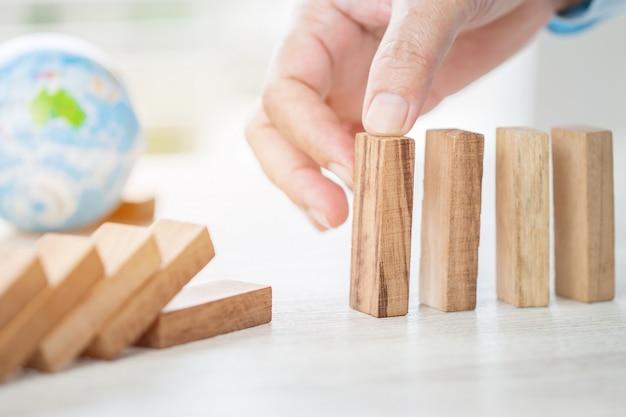 Rischio di pianificazione della strategia nel concetto di affari: uomo d'affari o ingegnere che dispone i domino del blocco di legno