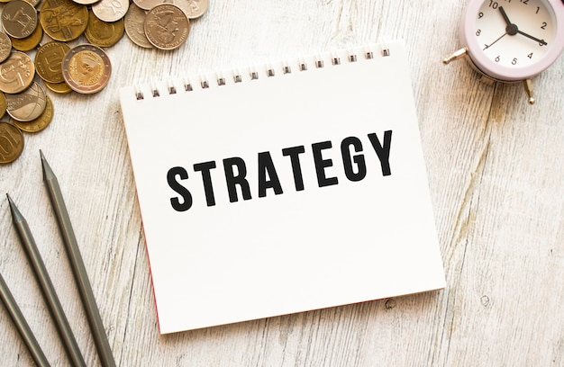 Testo di strategia su un foglio di blocco note. le monete sono sparse, matite su uno sfondo di legno grigio.