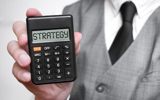 Iscrizione del testo di parola di strategia sulla calcolatrice in una mano maschio di un uomo d'affari in camicia bianca e cravatta blu