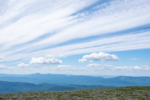Nubi di stratocumuli che si diffondono nel cielo su un altopiano di montagna, montagne blu in lontananza. nubi cumuliformi in natura. sfondo della natura, carta da parati, cartolina