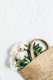 Borsa di paglia con fiori di peonia bianca su superficie bianca
