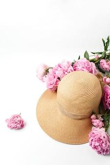 Cappello di paglia intrecciata, fiori di peonia rosa su bianco, vista dall'alto