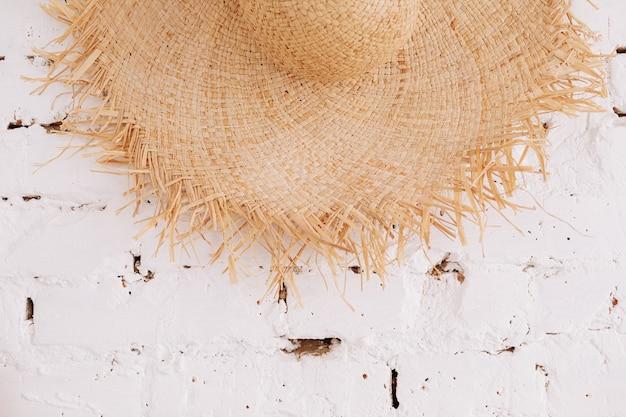 Un cappello di paglia sullo sfondo di un muro di mattoni bianchi con spazio per le copie. concetto di viaggio.