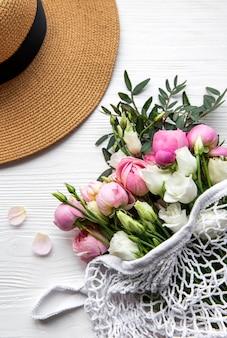 Cappello di paglia e bouquet di fiori di rosa rosa su sfondo bianco