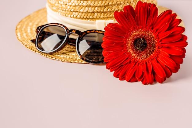 Cappello di paglia e fiori su sfondo rosa, concetto di viaggio di primavera