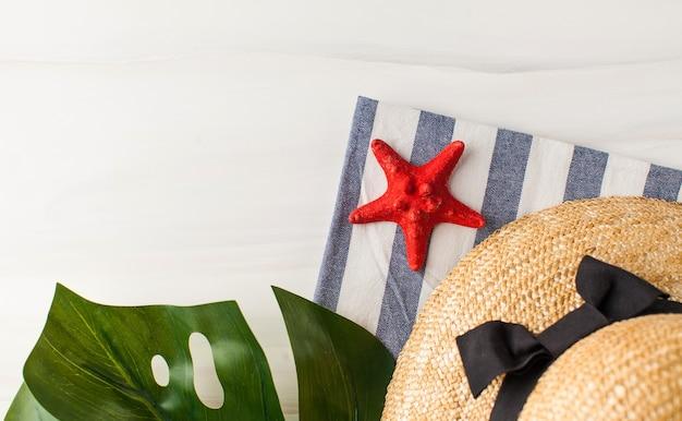 Un cappello di paglia foglia verde e una stella marina su bianco