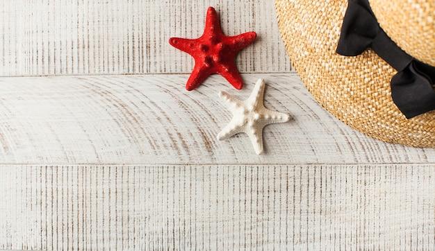 Un cappello di paglia e una stella marina su un tavolo di legno chiaro
