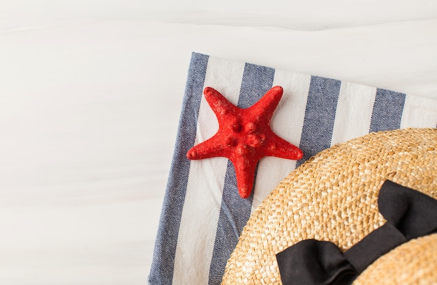 Un cappello di paglia e una stella marina su bianco